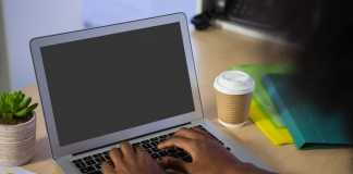 Cropped image of man using laptop in offce